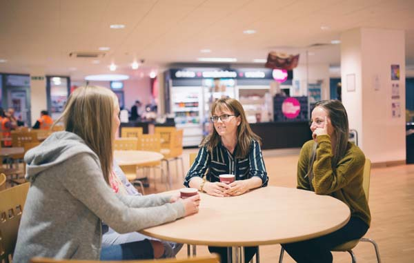 A Level students sitting with their tutor at Weston College